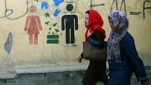 Zwei Frauen spazieren an Graffiti für Gleichberechtigung von Mann und Frau vorbei