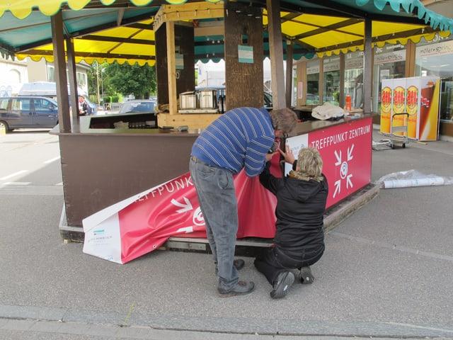 Zwei Leute befestigen Plakate an einem Infostand