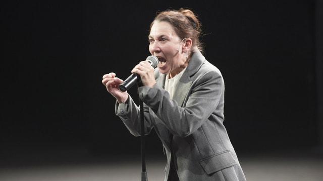 Eine Frau im Anzug spricht mit weit geöffnetem Mund und ernstem Blick in ein Mikrofon.
