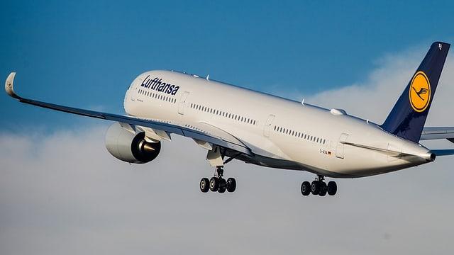 Lufthansa-Maschine im Steigflug kurz nach dem Abheben am Himmel mit Wolken