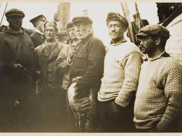 Vergilbte Schwarzweiss-Aufnahme: Männer stehen auf Schiff.