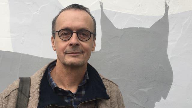 Der Wildtierbiologe Darius Weber vor einem Bild eines Luchses