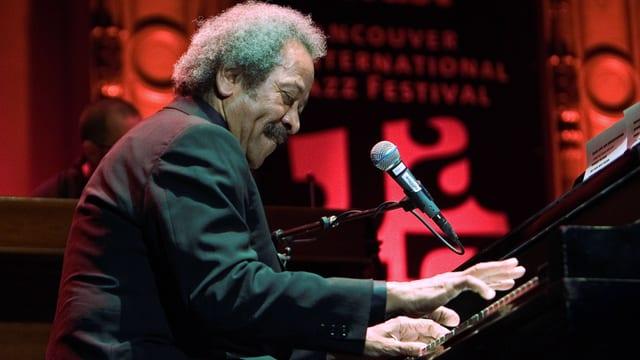 Mann mit grauem Haar haut in die Klaviertasten.