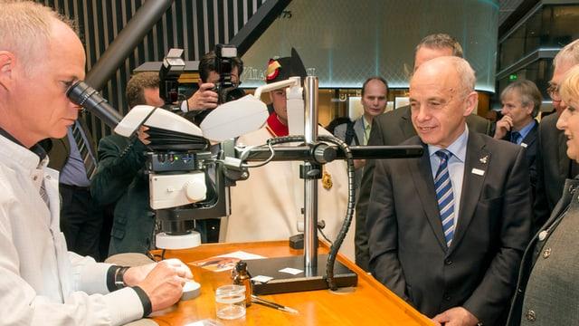Ein Uhrenmacher mit einem Mikroskoph arbeitet an einer Uhr. Bundesrat Ueli Maurer schaut interessiert zu.