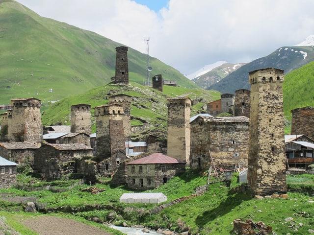 Das Dorf Ushguli in Georgien besteht aus ein paar wenigen Häusern und Türmen. Es ist umgeben von viel Grün.