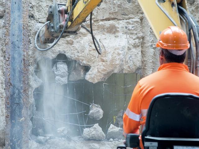 Ein Bauarbeiter schlägt mit seiner Maschine ein Loch in die Wand
