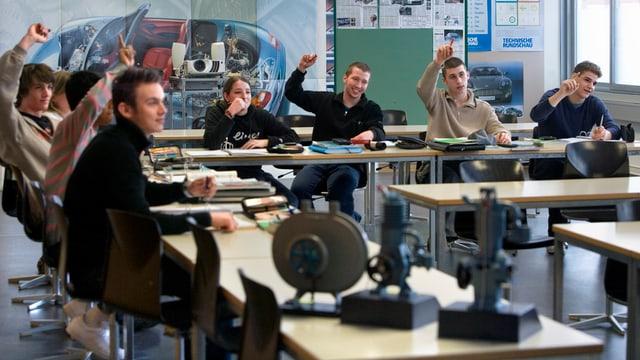 Schüler in Schulzimmer strecken Hände auf