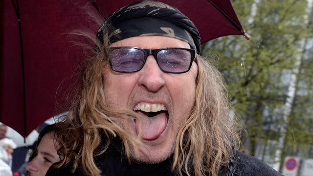 Mann mit Kopftuch und langen Haaren streckt Zunge raus
