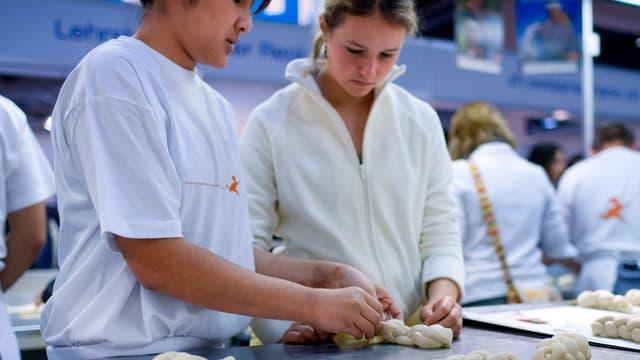 Jugendliche backen an einer Berufsmesse Zopf