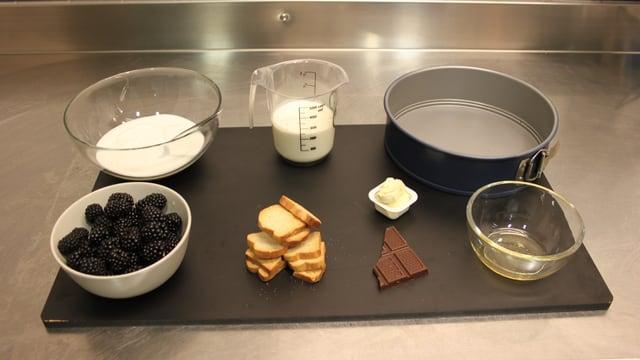 Die Zutaten für die Torte auf einem Bild: 30g Butter, 5 grosse Zwieback, 2-3 Stückchen Schokolade, 3dl Joghurt, 2-3 Esslöffel Honig, 200g Heidelbeeren, 2,5 dl Rahm