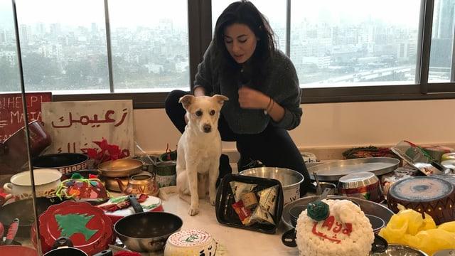 Künstlerin Hayat Nazer mit Hund Pucci in ihrem Atelier in Beirut. Sie hat Libanesinnen und Libanesen aufgefordert, alte Pfannen mit ihrem Namen, Wohnort und ihren Wünschen für Libanon zu  bemalen. Daraus will sie einen Weihnachtsbaum bauen, der ein Zeichen für Einigkeit und Frieden setzt.