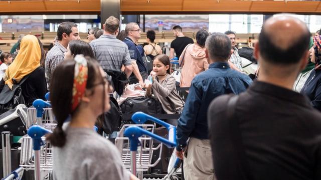 Menschen warten am Check-In-Schalter am Zürcher Flughafen, bis sie an der Reihe sind.