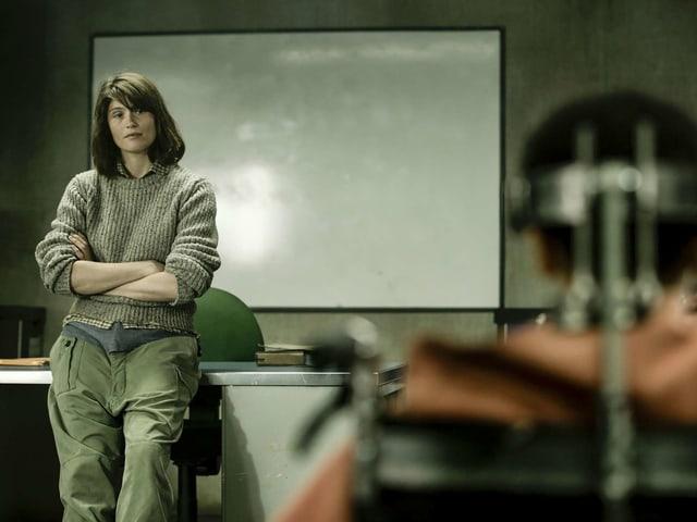 Eine Lehrerin lehnt an ihrem Pult, im Vordergund ein gefesseltes Mädchen.
