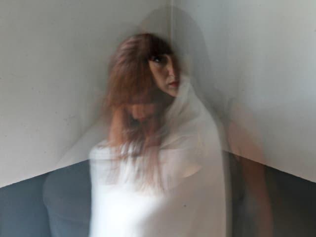 Eine Frau wickelt sich eine Decke ein. Gleichzeitig hat sie ihre Arme offen und ihr Gesicht zugewandt.