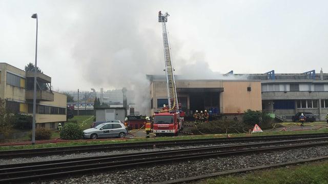 Feuerwehrwagen vor einer Industriehalle, aus der Rauch steigt.