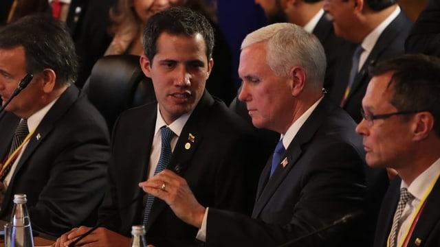 Zwei Männer reden an Gipfel miteinander.