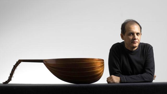 Anouar Brahem in schwarzem Pullover, an einem Tisch sitzend, auf dem seine Oud liegt.