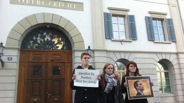 Drei Juso-Aktivistinnen mit einen ZKB-Kleber auf dem Maul, einem gerahmten Portrait von ZKB-Chef Scholl und ein Plakat mit dem Spruch: Fürchtet die Banken, ehret den König.