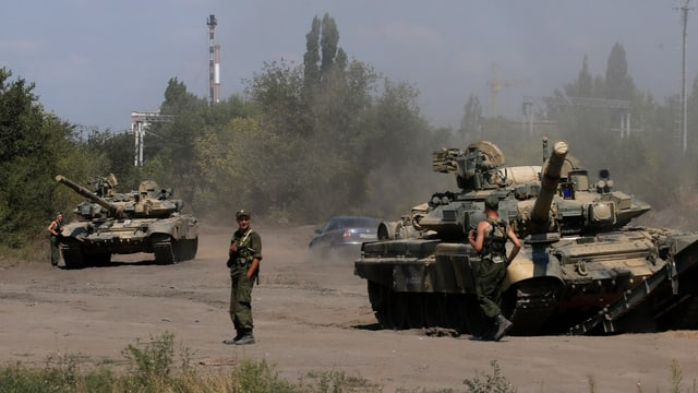 Zwei Panzer stehen auf einer Strasse, daneben zwei Soldaten