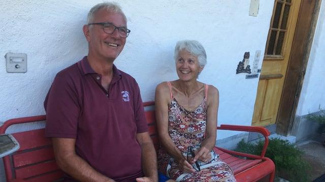 Eine Frau und ein Mann sitzen auf einer Bank vor ihrem Haus.