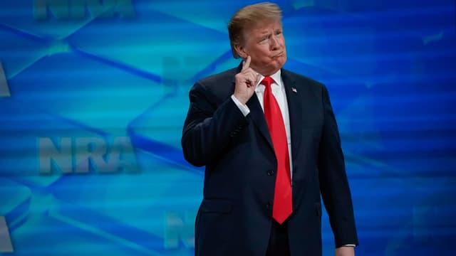 Donald Trump vor blauer Wand, wo das Logo der NRA steht.