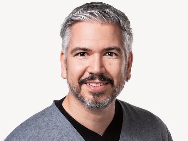 Ein Mann mit Bart und grauem Pullover.