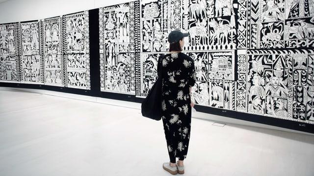 Eine junge Frau steht im Museum vor einem grossen schwarz-weissen Bild.
