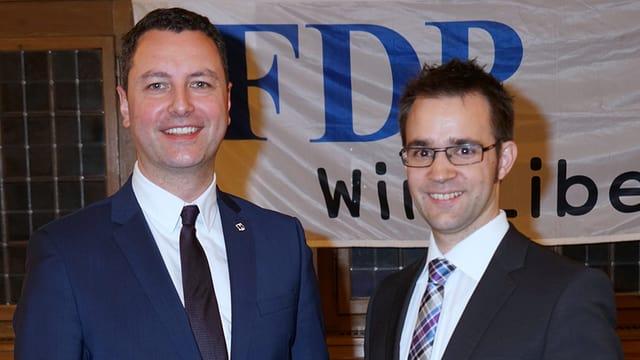Reto Wettstein und Titus Meier stehen vor einem FDP-Banner und lächeln.