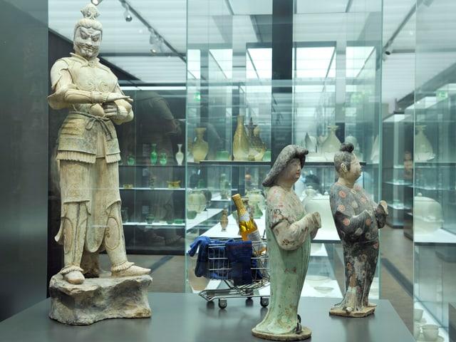 Chinesische Statuen in gläsernem Entrée, ein Einkaufswagen im Hintergrund