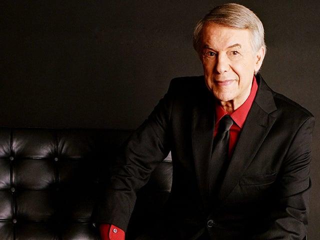 Ergrauter Mann mit rotem Hemd vor schwarmzem Hintergrund auf schwarzer Couch.