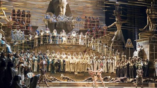 Opulente Bühne mt vielen in Gold gekleideten Schauspielern.
