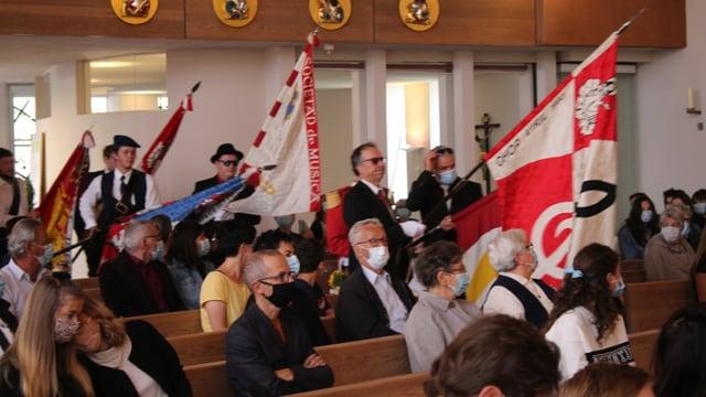 bandierels portan las bandieras en baselgia