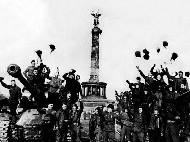 Zwei Panzer stehen vor einem Monument, umringt von vielen, jubelnden Menschen.