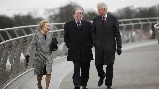 Drei Personen in festlicher Kleidung gehen über eine Brücke