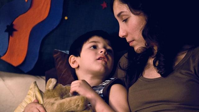 Ein kleiner Junge und eine Frau sitzen neben einander und schauen sich an.
