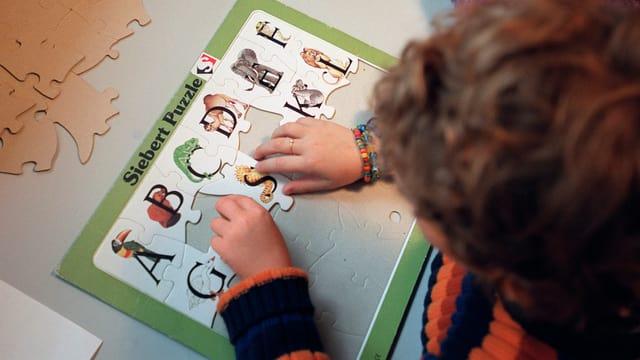 Ein Kind löst ein Puzzel