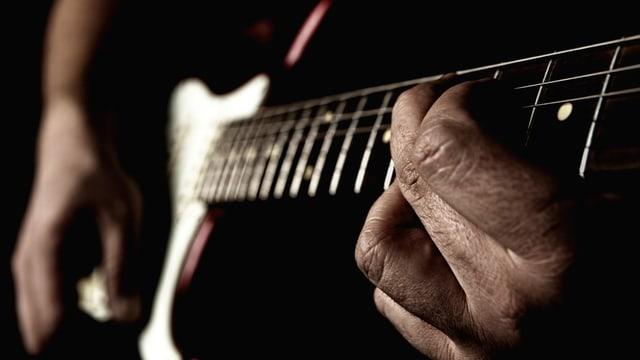 Blick auf zwei Hände, die Gitarre spielen
