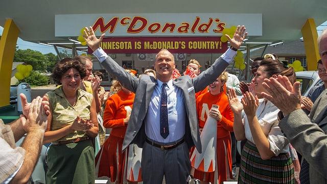 Mann streckt Hände in die Höhe, hinten McDonald Logo.