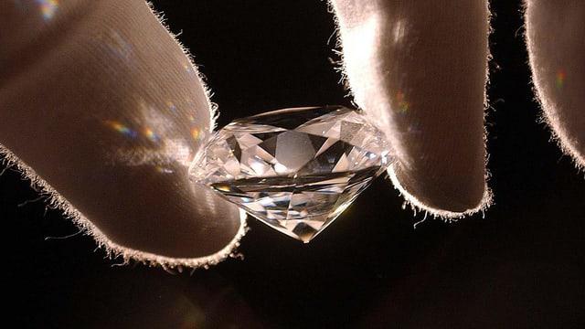 Behandschuhte Finger heben einen grossen Diamant.