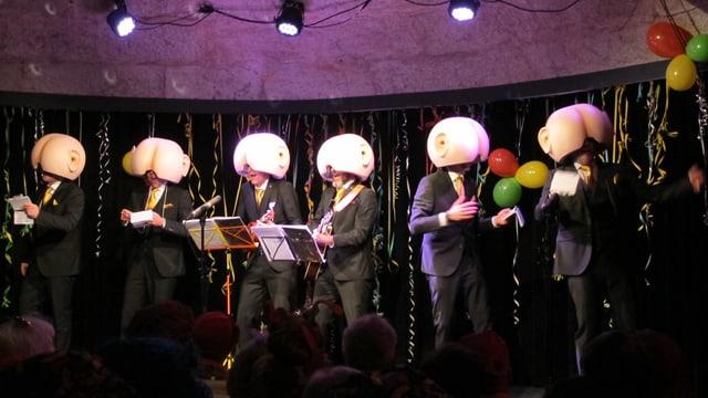 Männer in schwarzen Anzügen mit Gesäss-Masken.