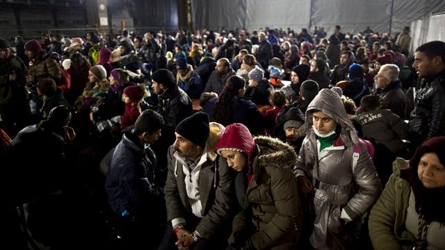 Gegen Hundert irakische Flüchtlinge warten in einer Halle auf einen Zug.