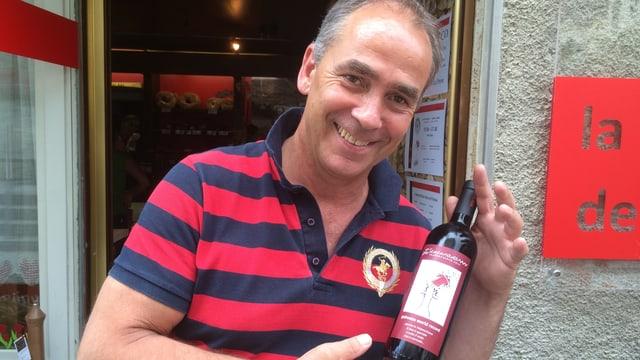 Orlando Lardi cun buttiglia da vin en maun