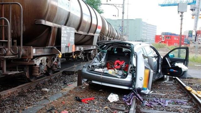 Ein beschädigtes Auto neben einem Zug auf einem ungesicherten Bahnübergang.