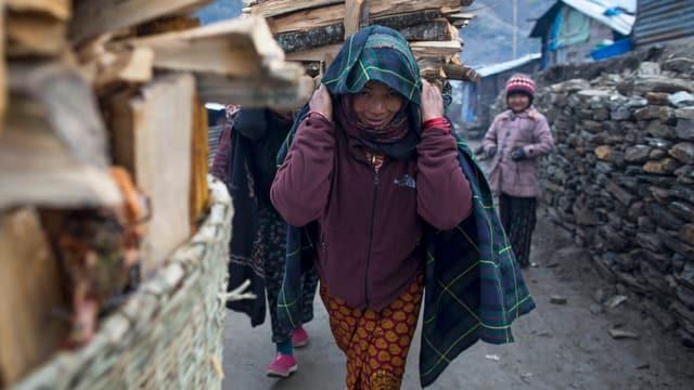 Nepalesische Frau schleppt Feuerholz.