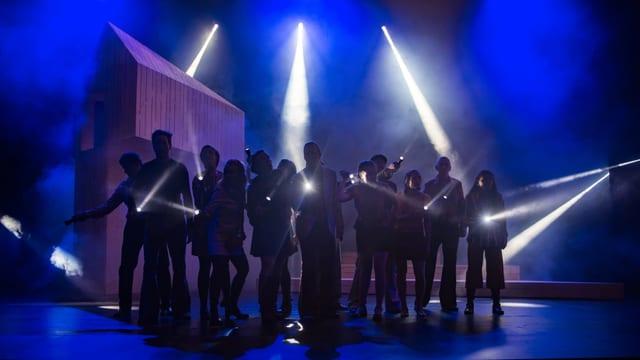Mehrere Menschen stehen beim Musical Umbra auf der Bühne, man sieht Taschenlampenlicht.