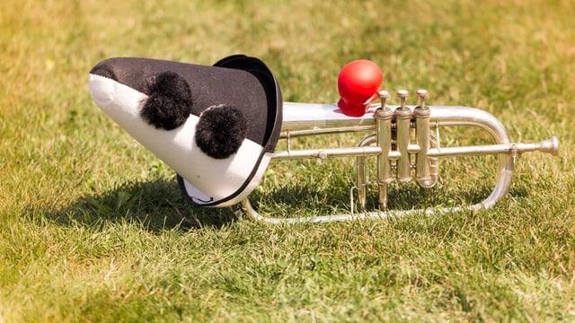 Trompete mit Narrenkappe und roter Nase auf einem Rasen