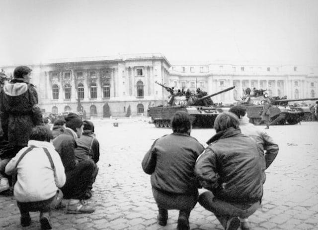 Menschen stehen vor dem Parlamentspalast in Bukarest, wo Panzer parkiert stehen