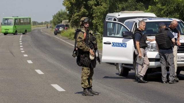 Soldat steht vor einem OSZE-Auto.