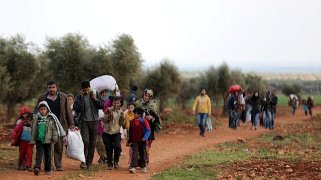 Menschen auf einem Feld, manche tragen Säcke.