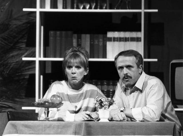 Ursula Schaeppi (links) und Walter Andreas Müller an einem Tisch, schauen verdutzt